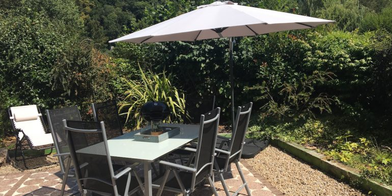 The secluded sun terrace equipped with garden furniture and BBQ